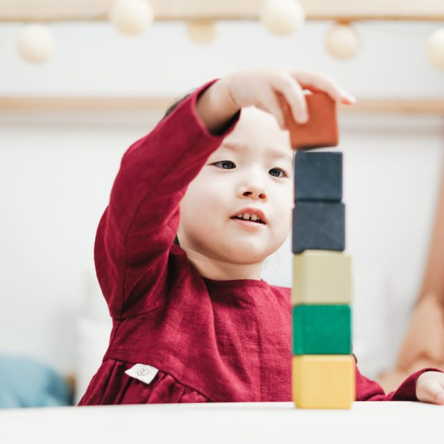 A little boy stacking blocks
