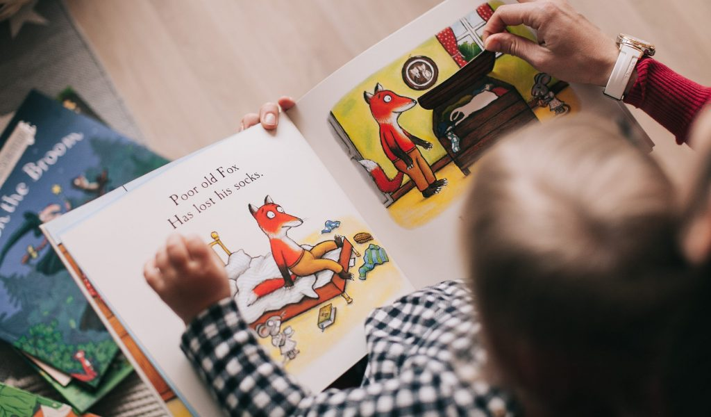 An adult reading a children's book to a child